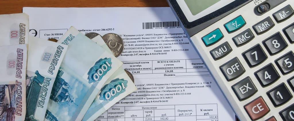 Квитанции об оплате, банкноты и калькулятор лежат на столе